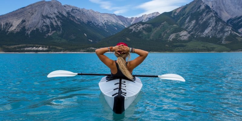 Woman on kayak gazing at mountains in the distance.