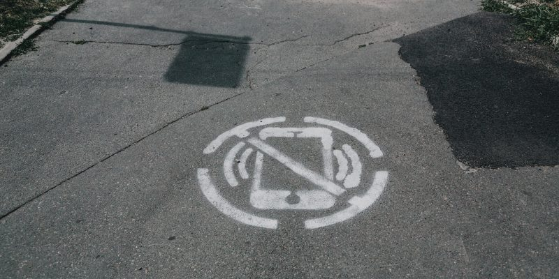 Image of a spray-painted on the pavement with a line through it.