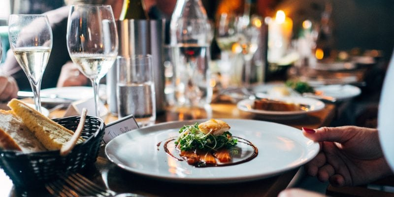 Food on ceramic plate with glass of white wine